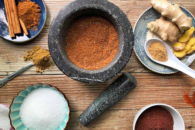 Horizontal image of various plates and bowls filled with spices and salts on a wooden table next to a gray mortar and pestle.