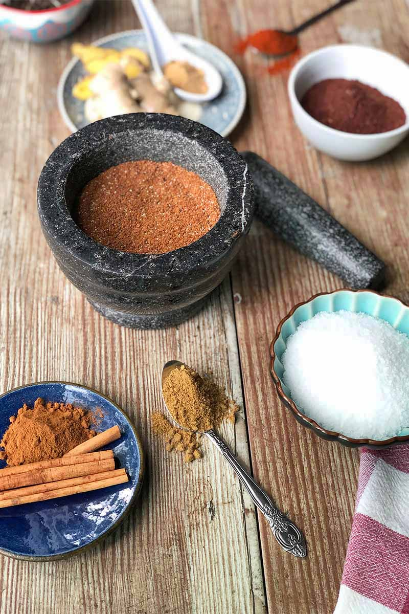 Vertical image of a gray mortar and pestle filled with a dark ground spice mixture on a wooden table surrounded by metal spoons with ground spices, a plate of cinnamon, a bowl of salt, and a plate of ginger.