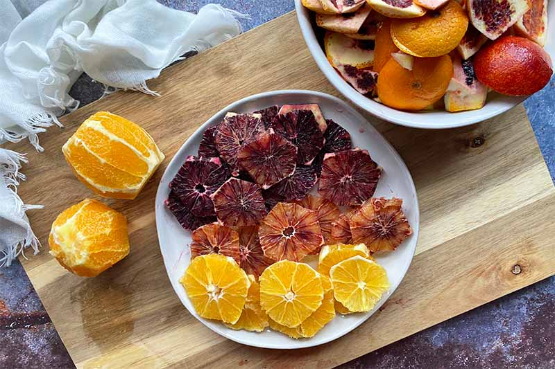 Horizontal image of assorted sliced citrus fruit on a plate on a wooden cutting board next to the peels in a bowl.