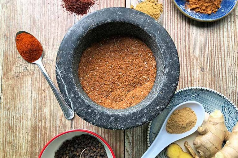 Horizontal image of a gray bowl filled with a deep orange powdery mixture on a wooden table next to spoons with spices, a plate of fresh ginger, and a bowl with whole peppercorns.