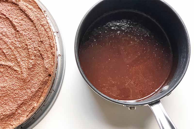 Horizontal image of a pot with a dark brown sauce next to a light brown dessert on a white surface.