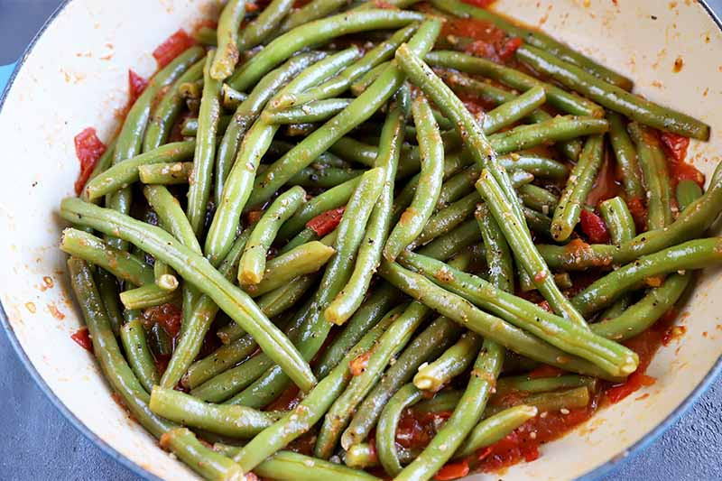 Horizontal image of green beans on top of chopped tomatoes in a pan.