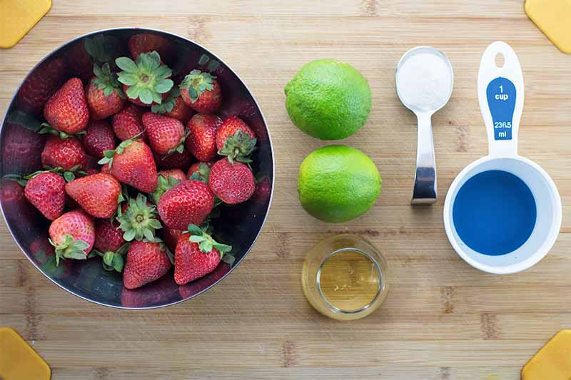 Horizontal image of a bowl of whole strawberries, two limes, a glass dish of honeys and measuring cups on a wooden cutting board with yellow corners.