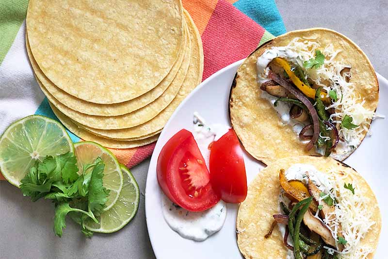Horizontal image of a stack of corn tortillas, slices of limes, and fresh herbs on a colorful towel next to a white plate with mixed cooked vegetables divided on two tortillas, sliced tomatoes, and a cream sauce.