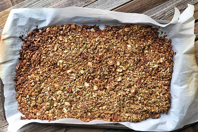 Horizontal image of a toasted cereal mixture on a baking sheet pan lined with parchment paper