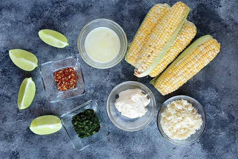 Horizontal image of ingredients to make elote antojitos on a gray surface.