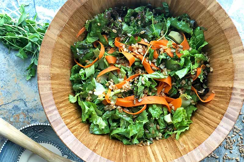 Horizontal image of a wooden bowl filled with a mixture of greens and vegetables.