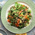 Horizontal image of a green-trimmed plate with mixed vegetables and grains next to more micro greens on the side.