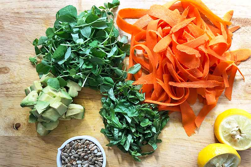 Horizontal image of carrot ribbons, chopped greens, cubed avocado, lemon wedges, and grains on a wooden board.