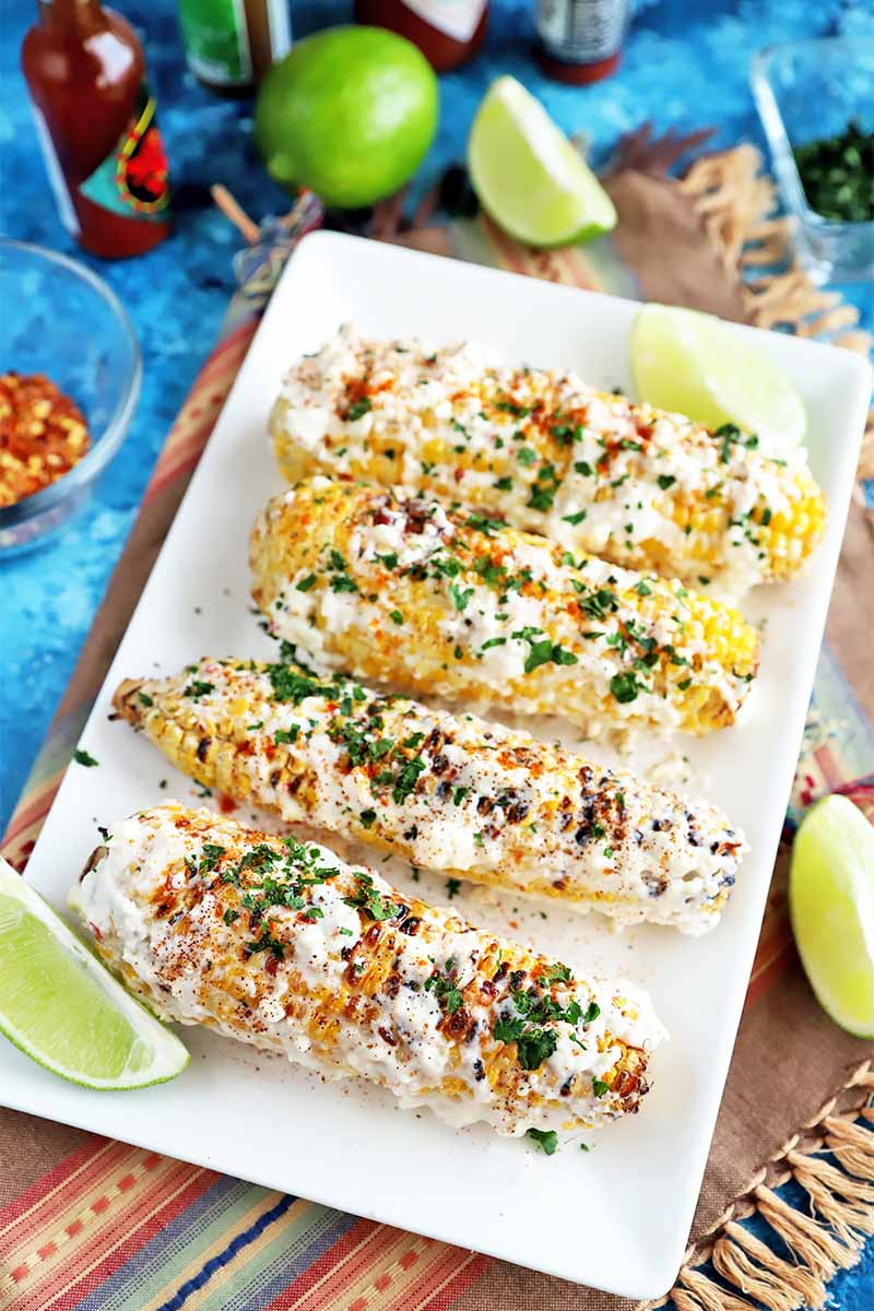 Vertical image of a row of grilled corn on a rectangular white plate next to whole and fresh limes on a colorful towel.