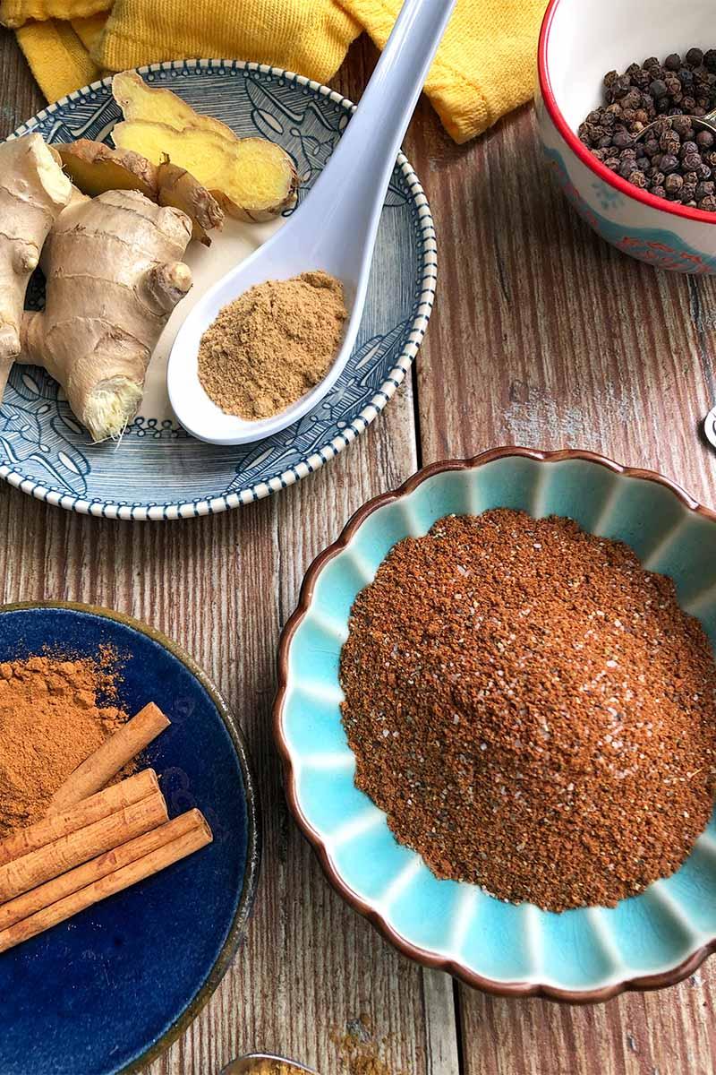 Vertical image of a blue bowl with a dark orange spice mixture next to a plate with fresh and ground ginger, a plate of cinnamon sticks and ground cinnamon, and a bowl of peppercorns.