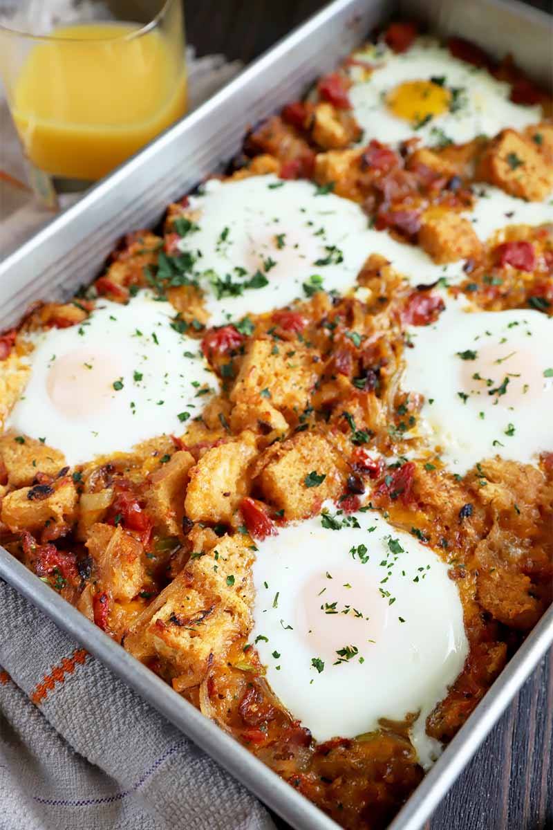 Vertical image of a casserole dish with cooked eggs over a bread and tomato mixture, with a chopped herb garnish on a towel.