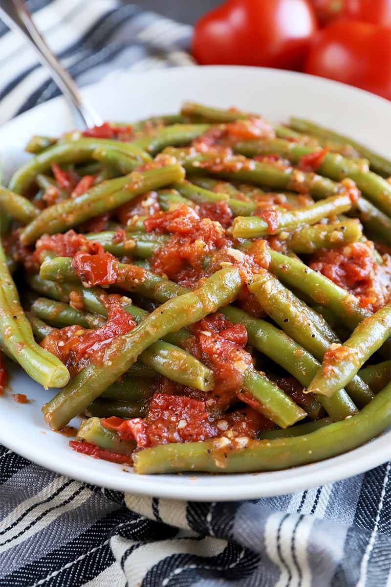 Vertical image of a white plate filled with green beans and tomatoes.