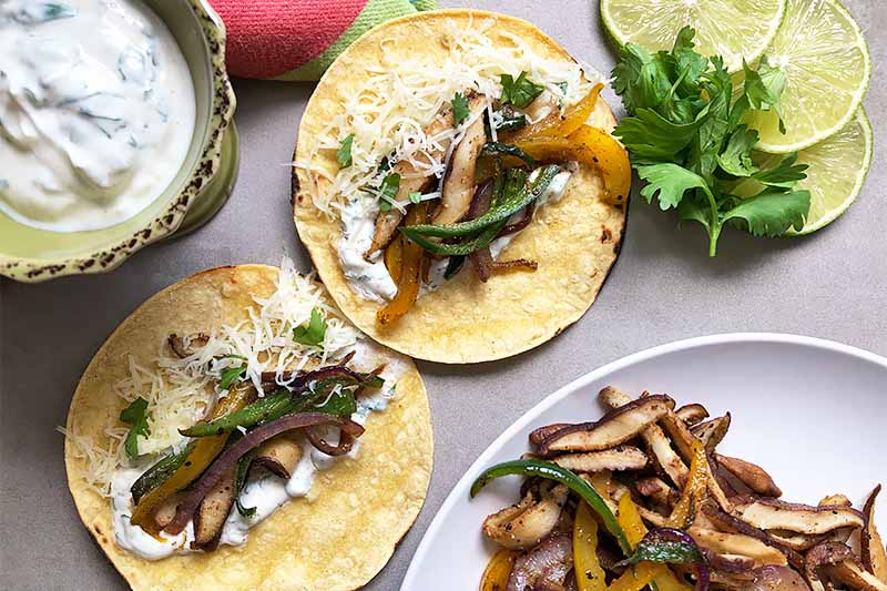 Horizontal image of two tacos with vegetables and cheese next to a green bowl of a cream sauce, limes, herbs, and a plate of cooked peppers and mushrooms.
