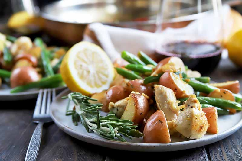 Horizontal image of two plates with potatoes, green beans, and cooked poultry pieces next to lemon wedges on a wooden table with a metal fork, towel, and glass of red wine.