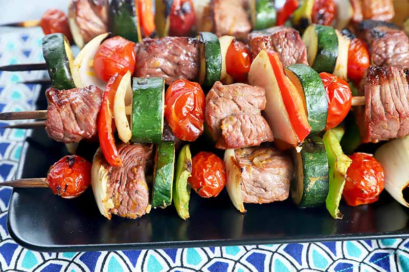 Horizontal close-up image of meat and veggie kebabs on a black plate on a colorful tablecloth.