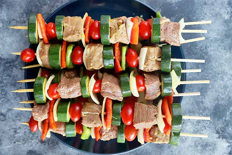 Horizontal image of assembled uncooked kebabs on a black plate.