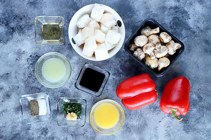 Horizontal image of fish pieces, mushrooms, whole peppers, and assorted seasonings in various dishes on a gray surface.