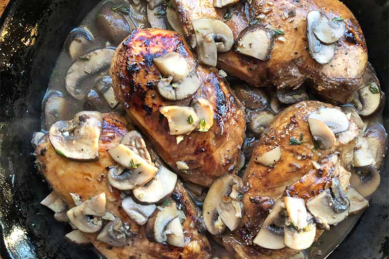 Horizontal image of cooking seasoned poultry breasts and mushrooms in a dark liquid in a pan.