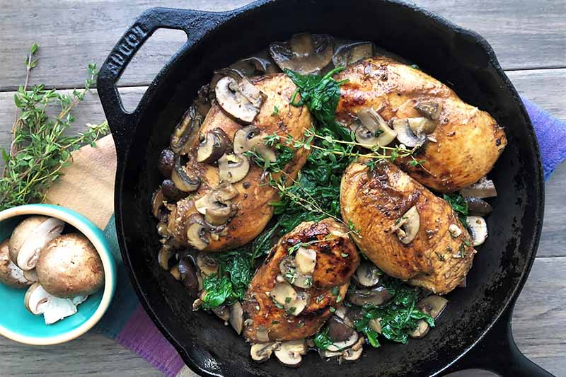 Horizontal image of a cast iron skillet with four cooked chicken breasts over a bed of spinach topped with mushrooms and sauce next to a bowl of garlic and a handful of fresh thyme.