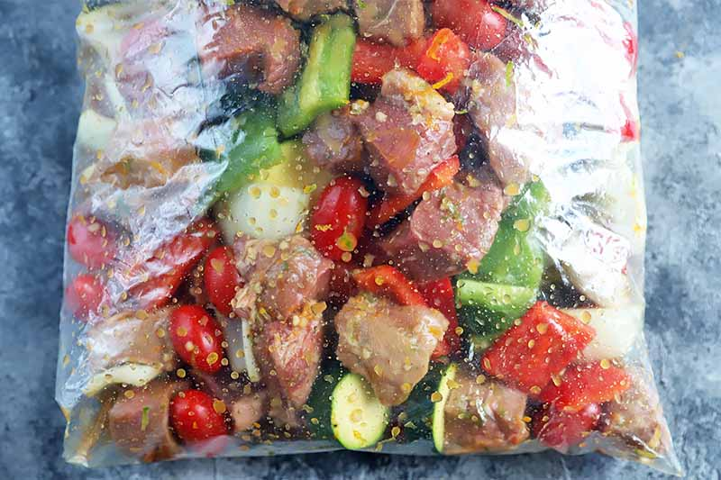 Horizontal image of a clear plastic bag filled with cubes of meat and chopped large vegetables in a marinade on a gray surface.