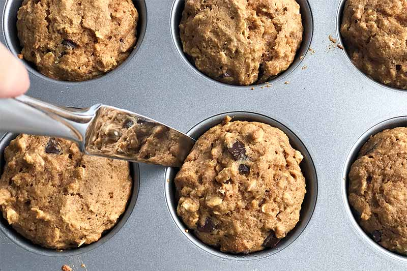 Horizontal image of a knife removing a baked muffin from a pan.