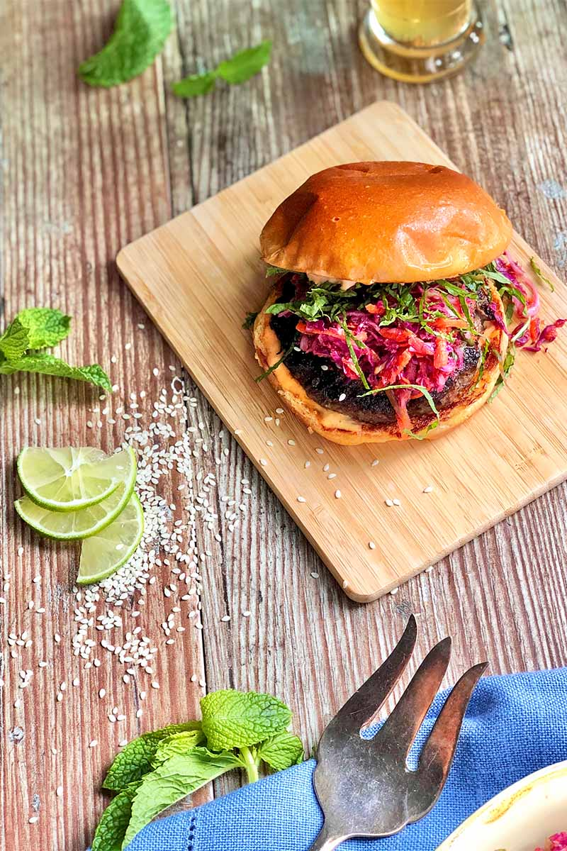 Vertical image of a burger with a hefty serving of slaw on top on a wooden board next to a blue napkin, limes, fresh herbs, a metal fork, and a blue towel.