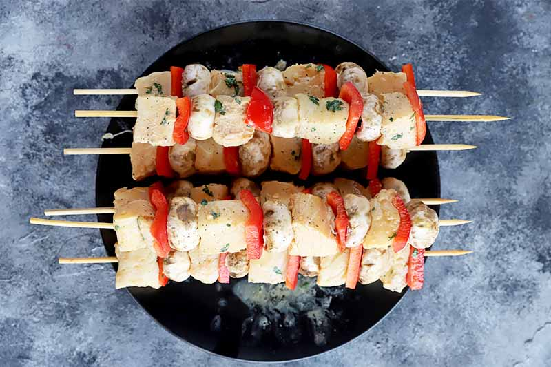 Horizontal image of uncooked seafood and vegetable skewers on a black plate.