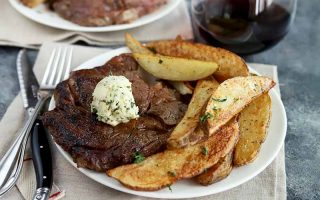 Horizontal image of a white plate with a seared large cut of beef topped with a dollop of herb butter next to potato wedges next to a glass of wine.