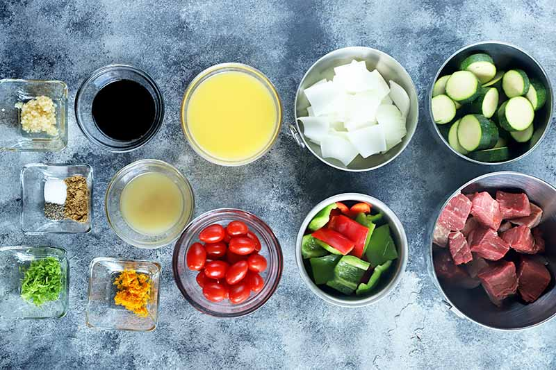 Horizontal image of various seasonings, vegetables, and cubed meat in bowls on a gray surface.