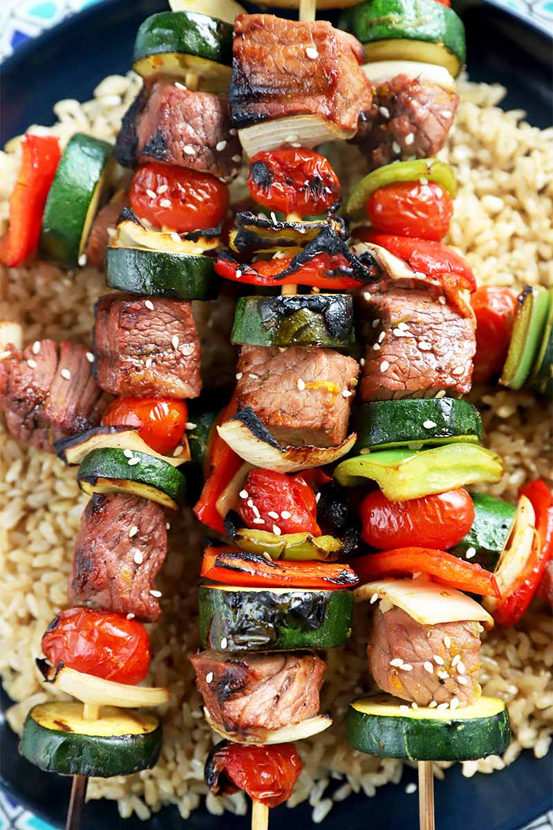 Vertical image of beef and veggie kebabs over brown rice on a black plate.