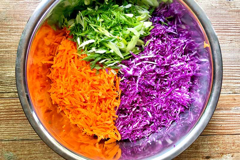 Horizontal image of colorful shredded vegetables divided by color in a metal bowl.