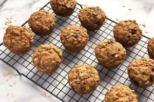 Horizontal image of three rows of oat and chocolate baked goods on a cooling rack on a white surface with scattered grains.
