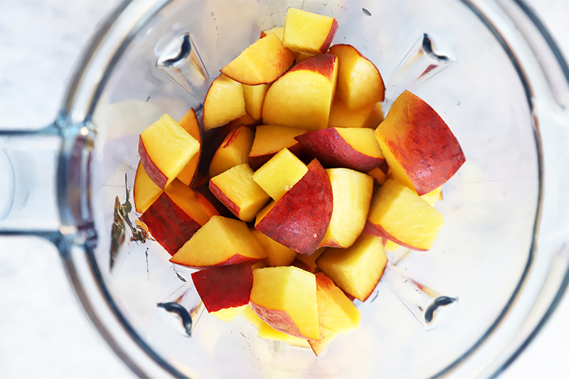 Horizontal image of cubed peaches in a blender.