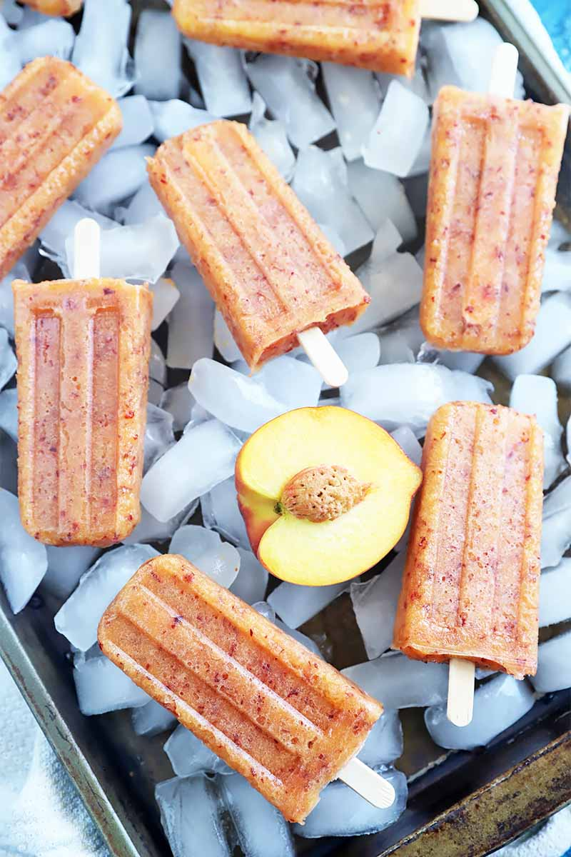 Vertical image of peach popsicles on top of ice on a baking sheet.