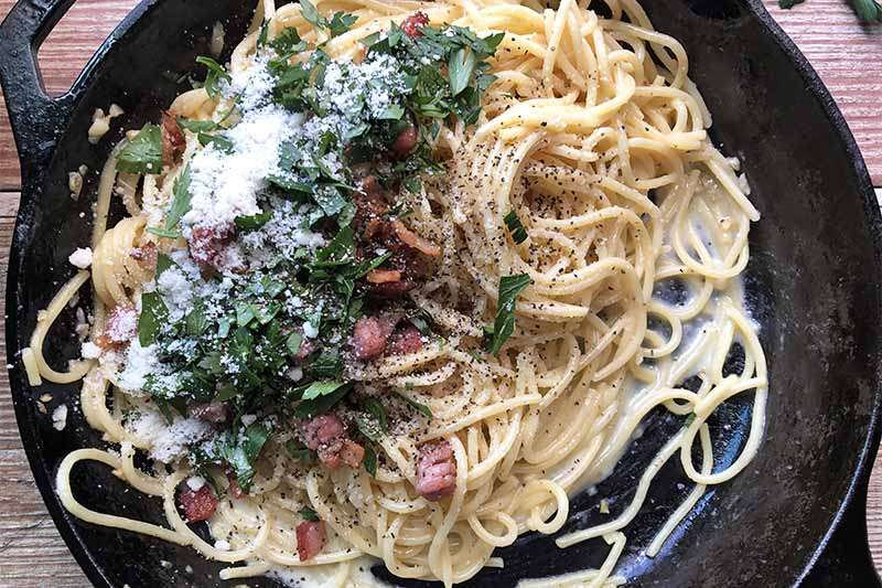 Horizontal image of small piles of bacon, parsley, and grated cheese on top of pasta in a pan.