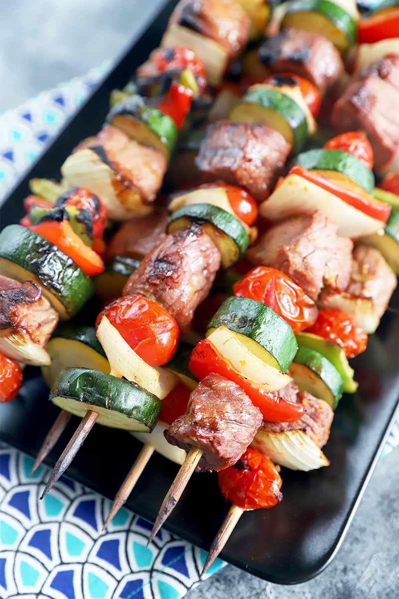 Vertical image of a stack of meat and vegetable kebabs on a black plate on a colorful blue tablecloth.