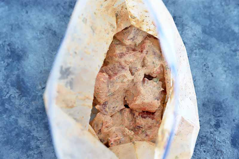 Horizontal image of cubed meat mixed in a creamy marinade in a plastic bag.