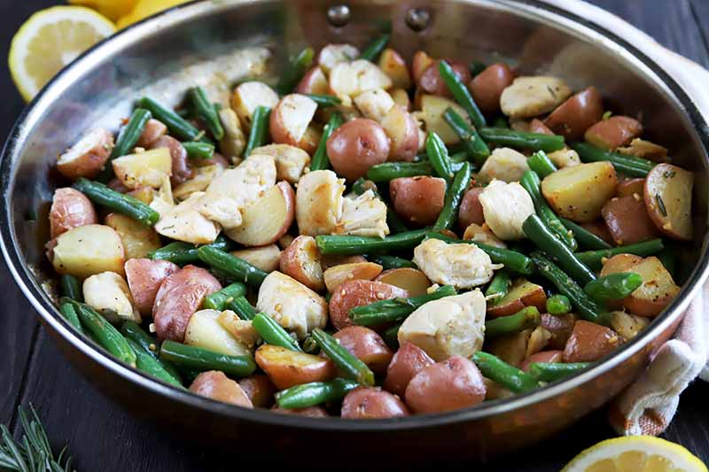 Horizontal image of a metal skillet filled with big pieces of chicken, spuds, and green beans.