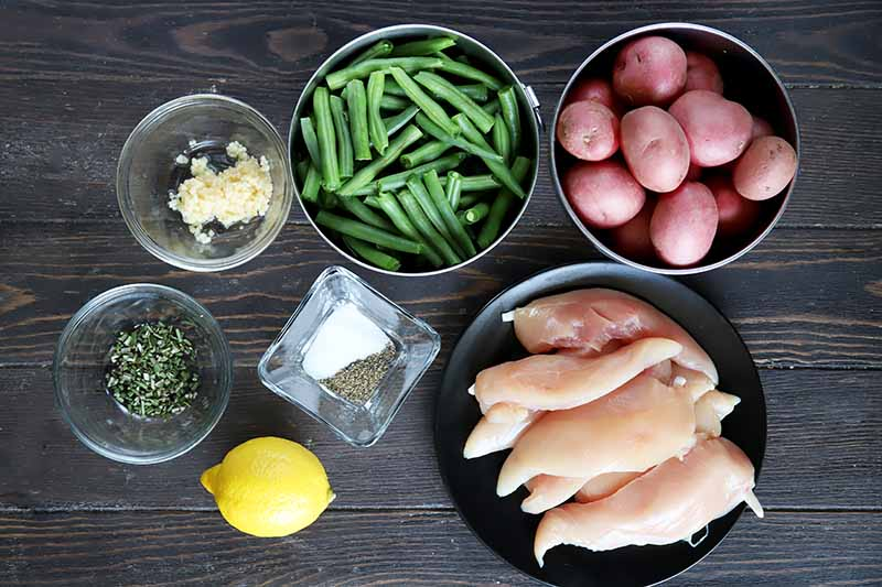Horizontal image of raw chicken, red potatoes, green beans, a lemon, and seasonings in bowls and plates on a dark wooden table.