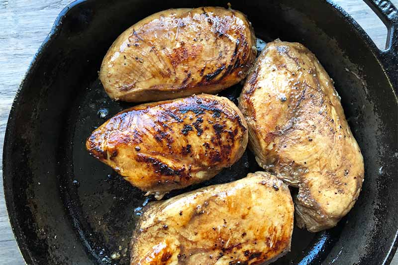 Horizontal image of searing poultry breasts in a cast iron skillet.
