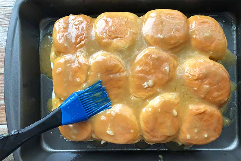 Horizontal image of brushing a row of buns with butter in a pan.