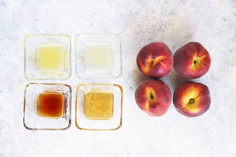 Horizontal image of four peaches and four measured ingredients in small glass bowls.