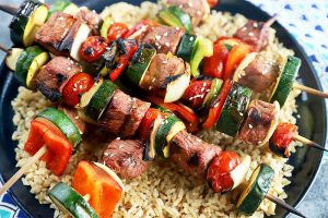 Horizontal image of pieces of beef and vegetables on sticks over brown rice on a black plate