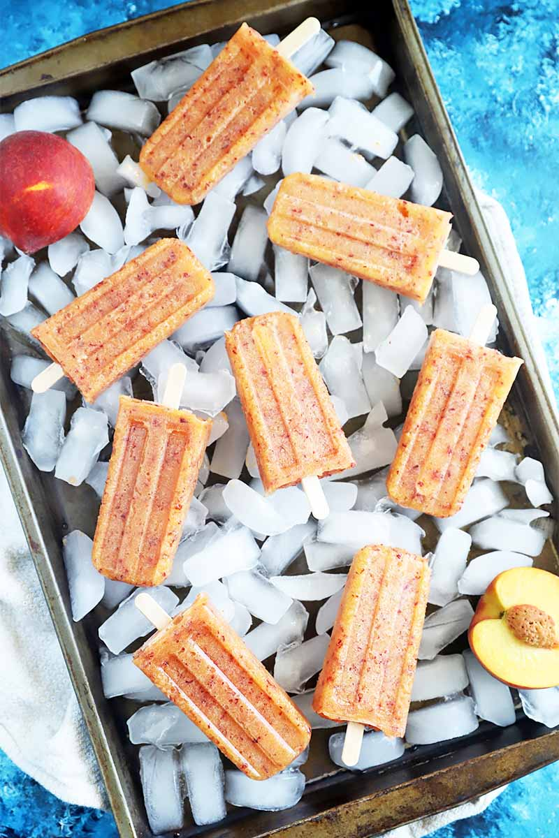 Vertical top-down image of a sheet pan filled with ice cubes with light orange frozen treats with sticks on top, all on a blue surface.