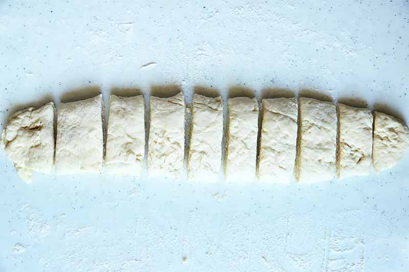 Horizontal image of a long piece of dough cut vertically in thin slices.