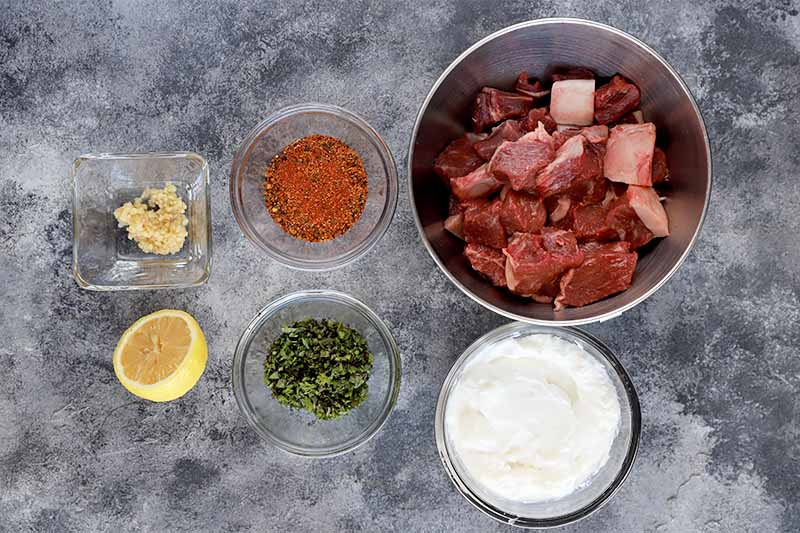 Horizontal image of a bowl of cubed raw meat, and bowls of yogurt and seasonings, and half of a lemon wedge on a gray surface.