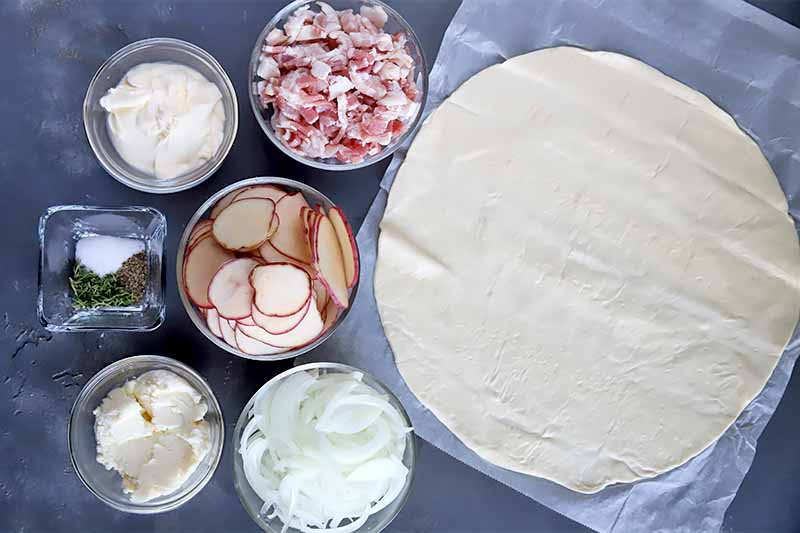 Horizontal image of a rolled out pizza dough and various prepped toppings in assorted glass bowls on a dark gray surface.