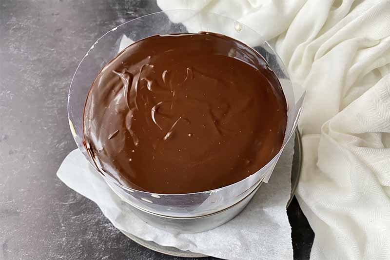 Horizontal image of a freshly made ganache on top of a dessert contained in a metal ring on parchment paper.