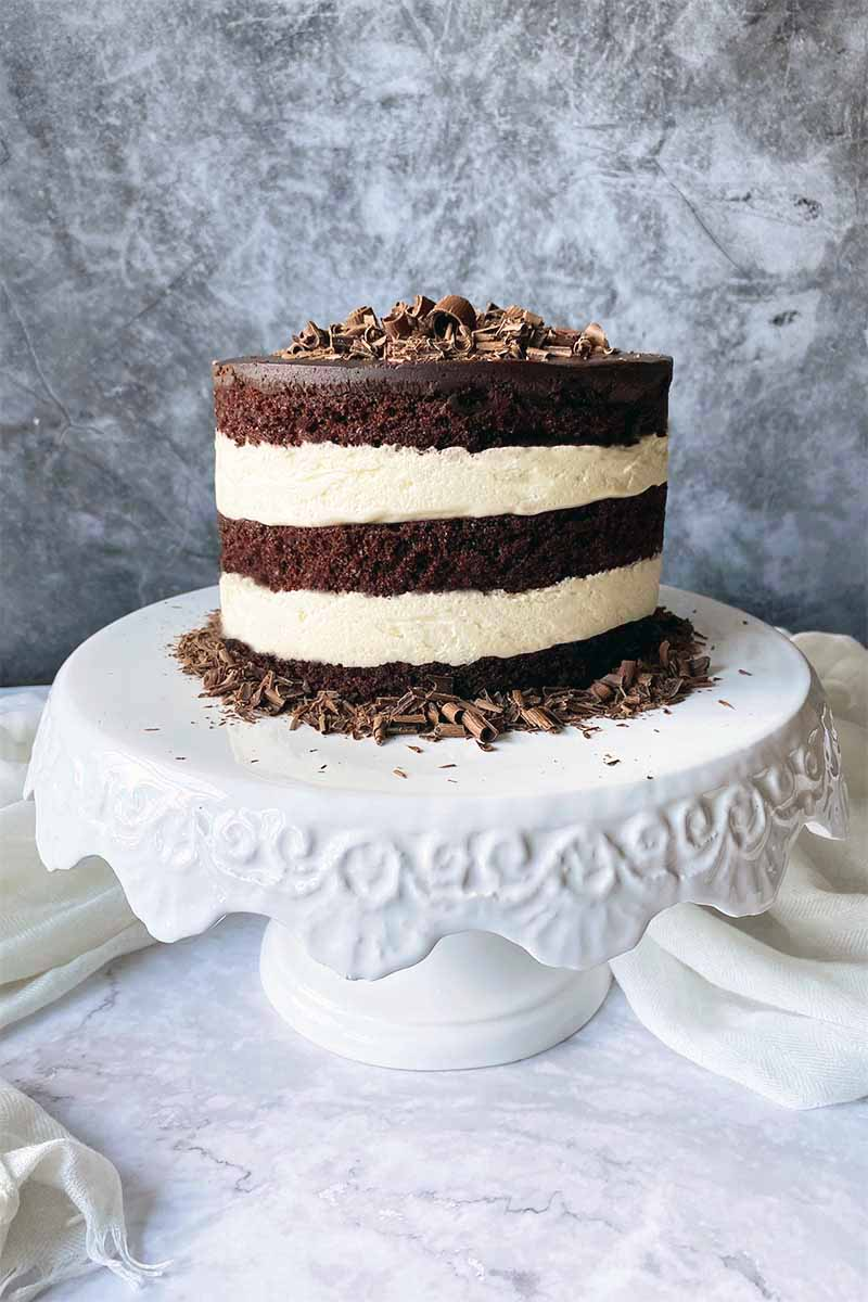 Vertical image of a round dessert with cocoa cake layers and vanilla cream layers garnished with chocolate shavings on a white cake stand.